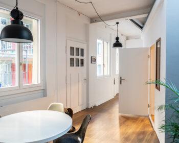 Tonstudio Audioflair GmbH. Entrée mit Mid-Century Tisch, Industrielampen, Eames Stuehle und Fensterfront. Ihr Partner für Werbung, Musik und Sounddesign