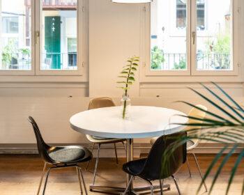 Tonstudio Audioflair GmbH. Lounge mit Mid-Century Tisch, Industrielampen, Eames Stühlen und Fensterfront. Ihr Partner für Werbung, Musik und Sounddesign