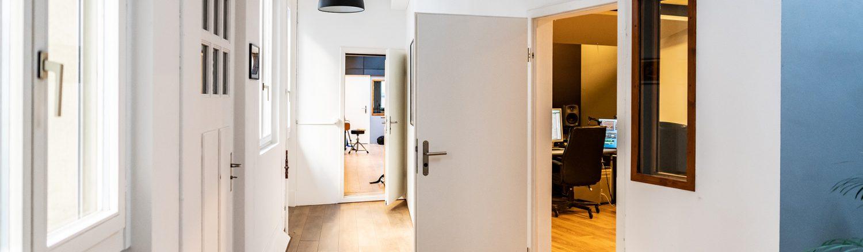 tonstudio-audioflair-gmbh-korridor-mit-tisch-industrielampen-und-eames-stuehlen-sicht-auf-piano-im-aufnahmeraum_light
